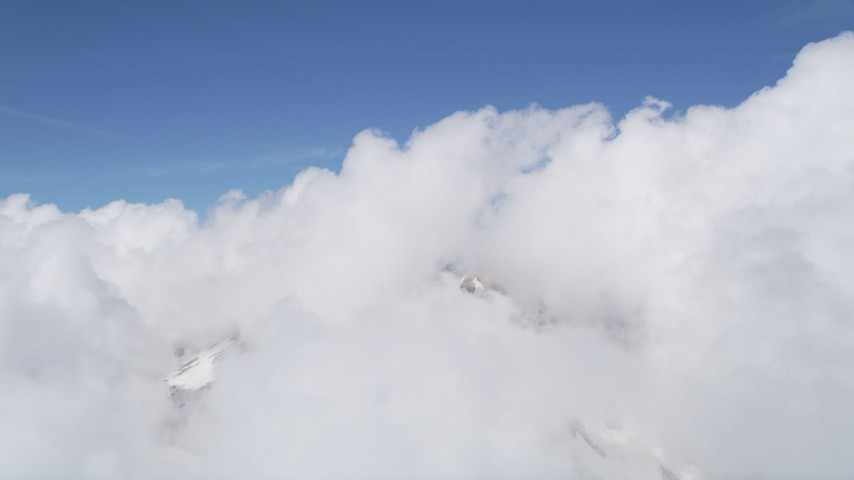 5K aerial video of thick clouds atop Mount St. Helens, reveal snowy slopes, Washington Aerial Stock Footage | AX52_056