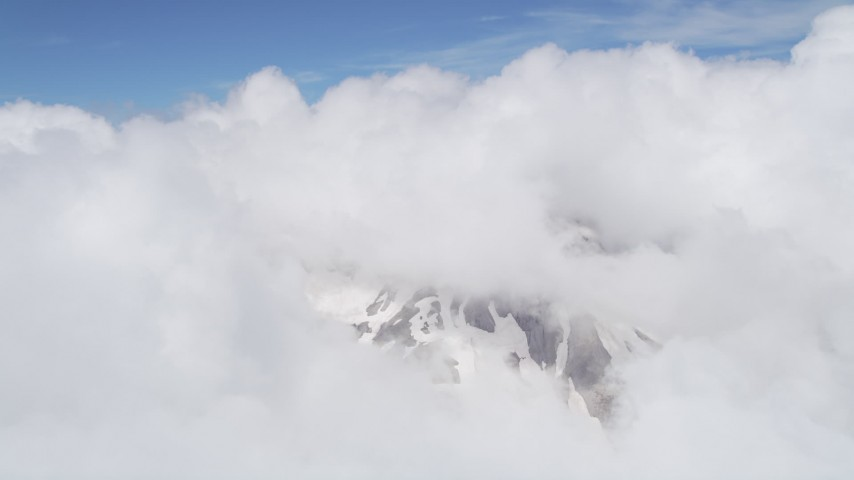 5K stock footage aerial video of snowy slopes of Mount St. Helens peeking through cloud coverage, Washington Aerial Stock Footage | AX52_057