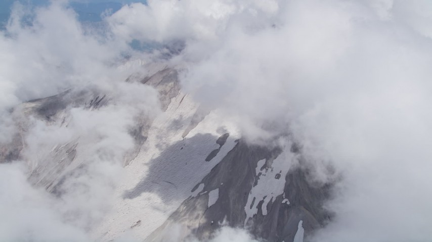 5K stock footage aerial video orbit thick clouds to reveal snow on Mount St. Helens' slopes, Washington Aerial Stock Footage | AX52_059