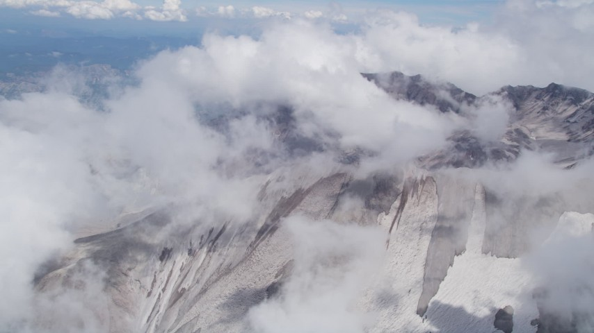 5K aerial video orbit the Mount St. Helens crater with snow and low clouds, Washington Aerial Stock Footage | AX52_060