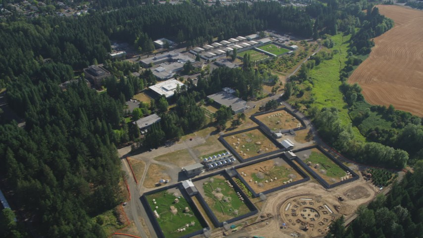 5K stock footage aerial video of flying by fields and the Oregon National Primate Research Center, Hillsboro Aerial Stock Footage | AX53_002