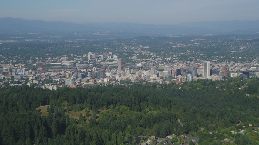 5K stock footage aerial video of flying over wooded hills toward city buildings, Downtown Portland, Oregon Aerial Stock Footage | AX53_012