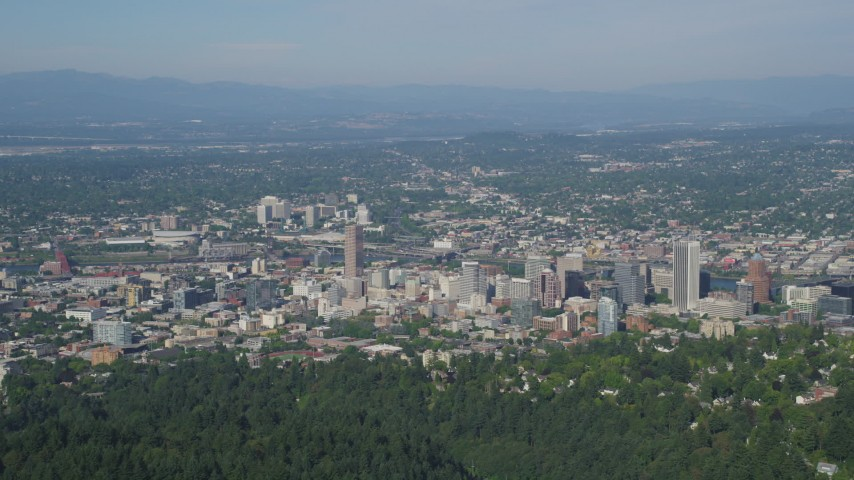 5K aerial video fly over wooded hills toward city buildings, Downtown Portland, Oregon Aerial Stock Footage | AX53_013