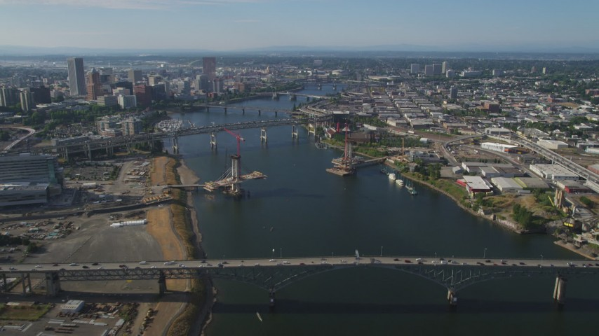 5K stock footage aerial video fly over Ross Island Bridge spanning Willamette River toward Downtown Portland, Oregon Aerial Stock Footage | AX53_072