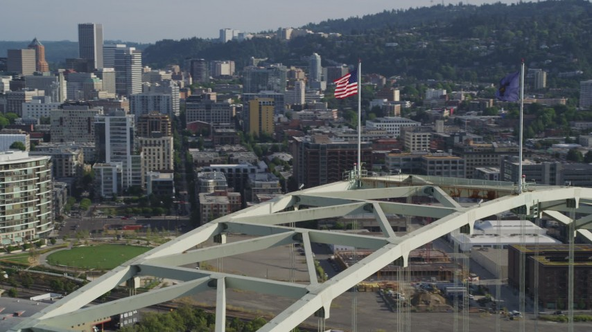 5K stock footage aerial video of approaching American flag atop Fremont Bridge and pan to reveal Downtown Portland, Oregon Aerial Stock Footage | AX53_082