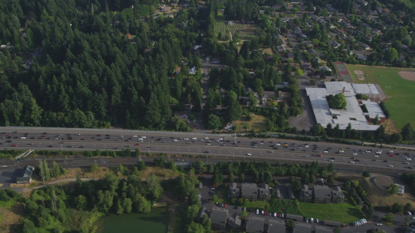 5K stock footage aerial video fly by heavy highway traffic, a school and park, Southwest Portland, Oregon Aerial Stock Footage | AX53_092