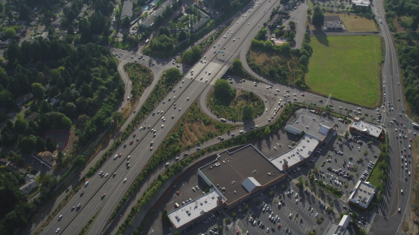 5K stock footage aerial video fly over shopping center and tilt to bird's eye of light traffic on highway, Southwest Portland, Oregon Aerial Stock Footage | AX53_095