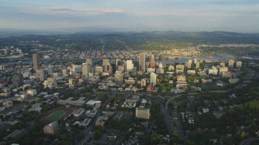 5K stock footage aerial video of flying by downtown buildings beside the Willamette River, Downtown Portland, Oregon, sunset Aerial Stock Footage AX54_019