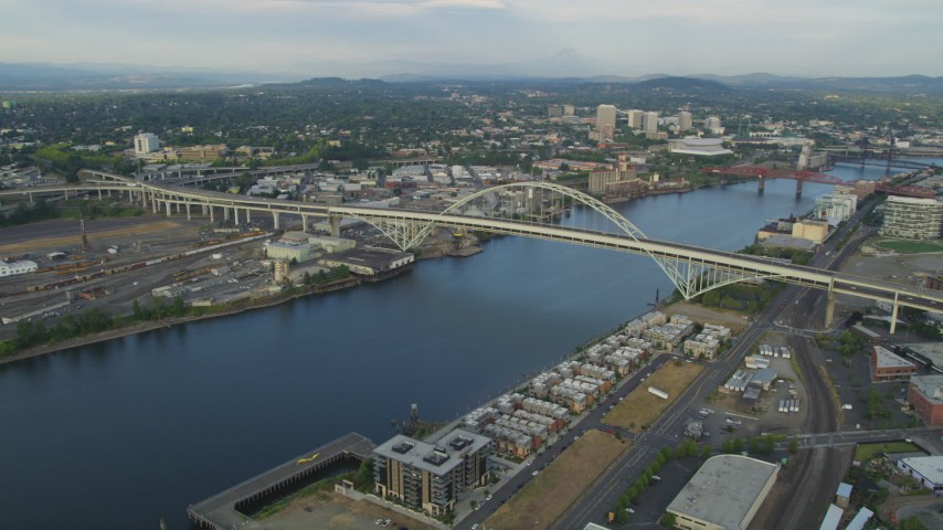 5K stock footage aerial video of flying by Fremont Bridge, spanning Willamette River, Downtown Portland, Oregon, sunset Aerial Stock Footage   AX54_022