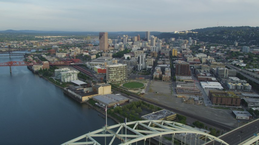Flying over the Fremont Bridge, approaching Downtown Portland, Oregon, sunset Aerial Stock Footage | AX54_024