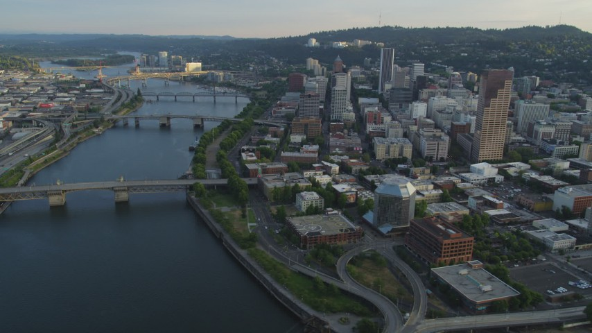 5K stock footage aerial video of flying by city bridges across the Willamette River, Downtown Portland, Oregon, sunset Aerial Stock Footage | AX54_030