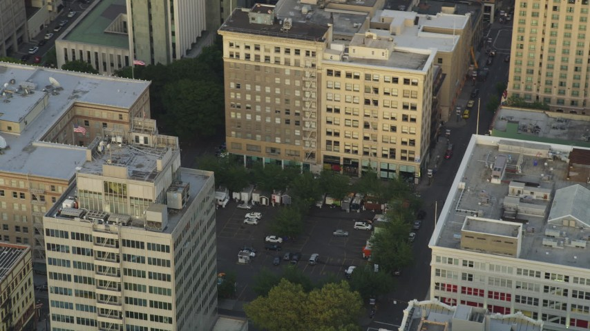 5K stock footage aerial video of orbiting a parking lot by office buildings in Downtown Portland, Oregon, sunset Aerial Stock Footage | AX54_041