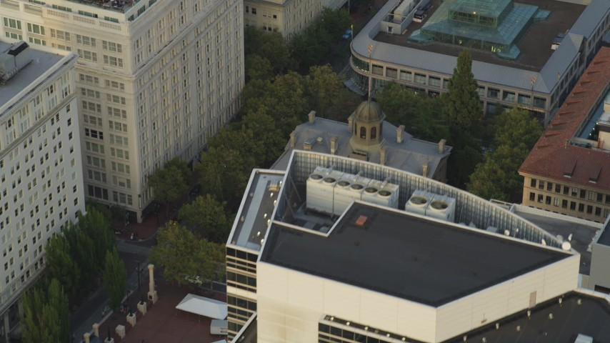 Flying over a skyscraper, revealing Pioneer Courthouse, Portland, Oregon, sunset Aerial Stock Footage | AX54_042