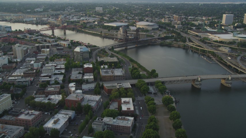 5K stock footage aerial video of flying by bridges spanning the Willamette River near Memorial Coliseum and Moda Center, Downtown Portland, Oregon, sunset Aerial Stock Footage | AX54_044