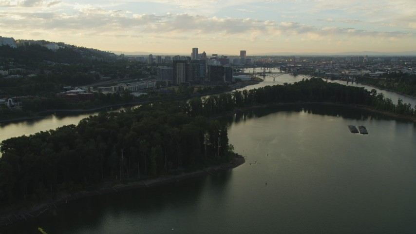 5K stock footage aerial video of flying by Ross Island, South Waterfront, Downtown Portland, Oregon in the distance, sunset Aerial Stock Footage | AX54_053
