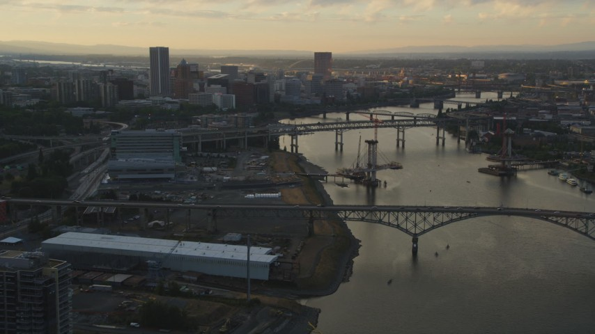 5K aerial  video tilt from Willamette River, reveal bridges and Downtown Portland, Oregon, sunset Aerial Stock Footage | AX54_054