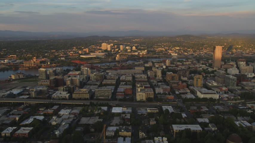 5K stock footage aerial video of a view of downtown buildings, Lloyd District and the Willamette River at sunset, Downtown Portland, Oregon Aerial Stock Footage | AX54_060