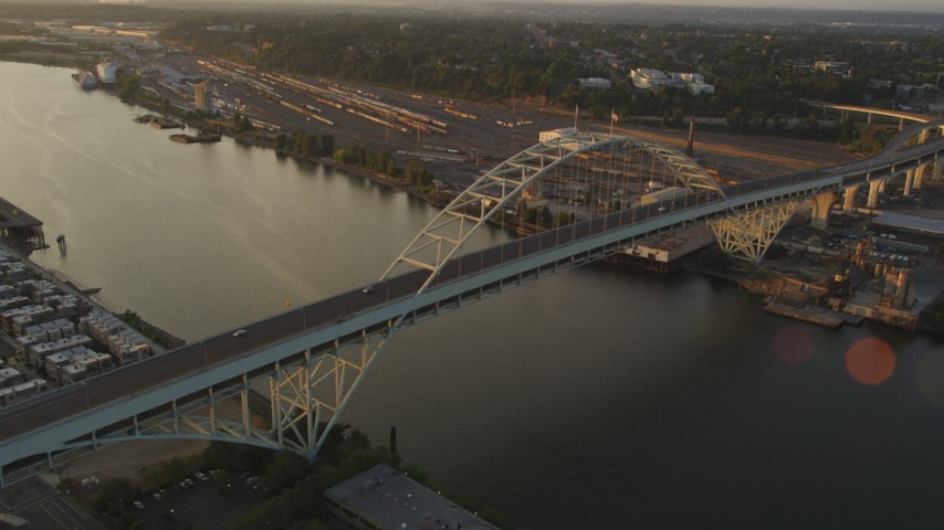 5K stock footage aerial video of passing the Fremont Bridge, Downtown Portland, Oregon, sunset Aerial Stock Footage | AX54_062
