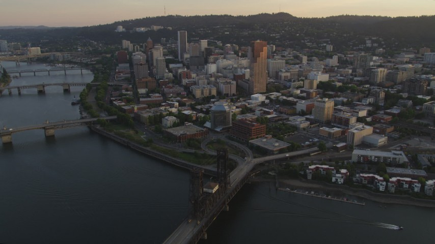 5K aerial video fly by downtown, over Willamette River, Steel Bridge, Downtown Portland, Oregon, sunset Aerial Stock Footage | AX54_067