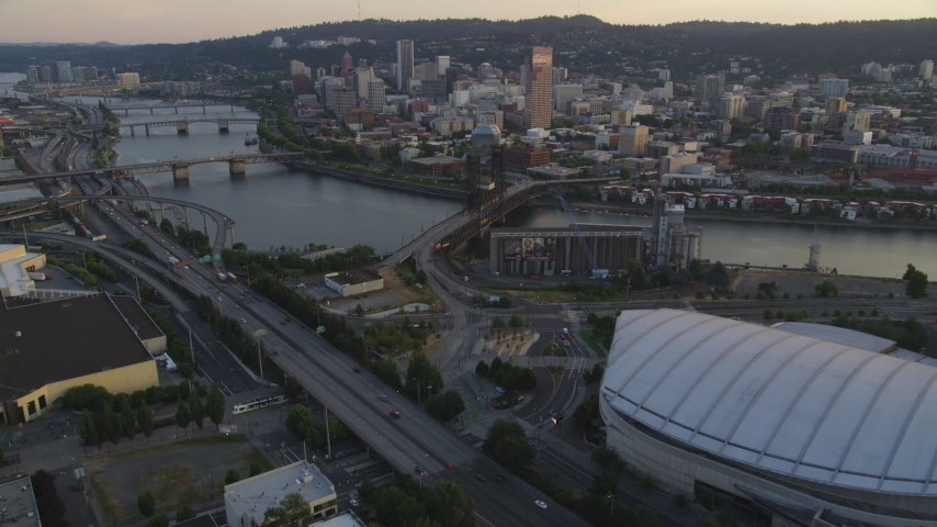 5K aerial video approach and fly over Rose Garden Arena, Steel Bridge, Downtown Portland, Oregon, sunset Aerial Stock Footage | AX54_074