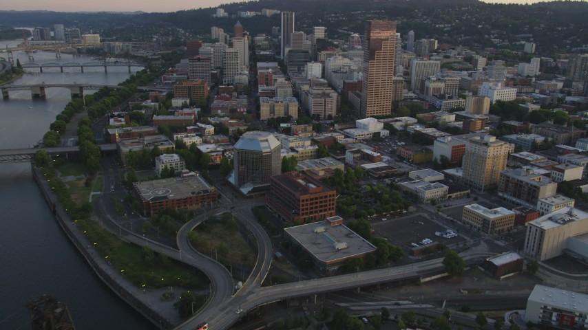 5K stock footage aerial video fly over Steel Bridge to approach US Bancorp Tower, Downtown Portland, Oregon, sunset Aerial Stock Footage | AX54_075
