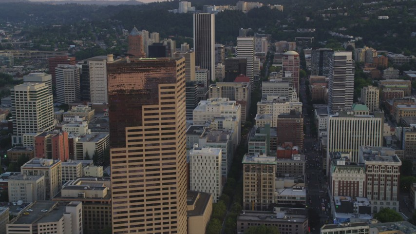 5K stock footage aerial video of flying by US Bancorp Tower and city streets in Downtown Portland, Oregon, sunset Aerial Stock Footage | AX54_076