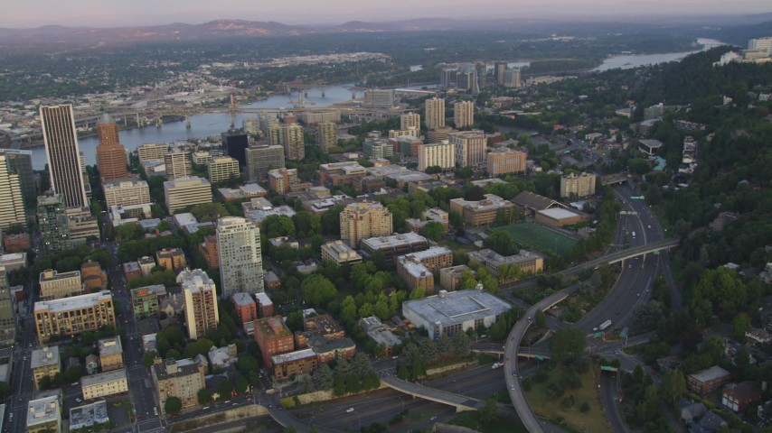 5K aerial video of flying by skyscrapers and Portland State University in Downtown Portland, Oregon, sunset Aerial Stock Footage | AX54_079