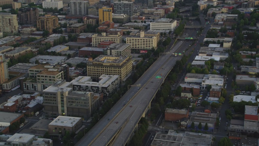 5K stock footage aerial video track cars on Interstate 405, tilt to reveal skyscrapers in Downtown Portland, Oregon, sunset Aerial Stock Footage | AX54_085
