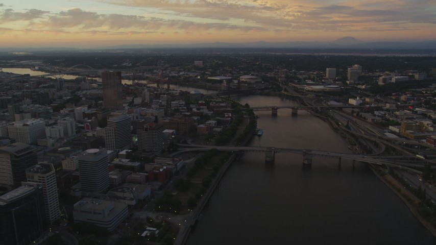 5K stock footage aerial video of following the Willamette River over bridges, Downtown Portland, Oregon, twilight Aerial Stock Footage | AX54_096