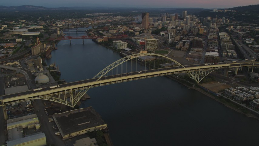 5K stock footage aerial video pan across the Fremont Bridge, revealing Downtown Portland, Oregon, twilight Aerial Stock Footage | AX54_101