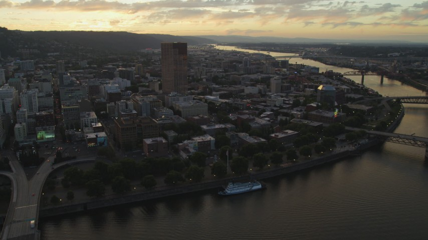 5K stock footage aerial video of US Bancorp Tower and Willamette River bridges, Downtown Portland, Oregon, sunset Aerial Stock Footage | AX54_105