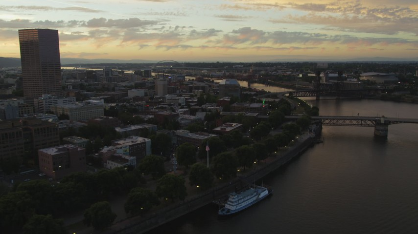 5K stock footage aerial video follow the Willamette River toward the White Stag Sign in Downtown Portland, Oregon, sunset Aerial Stock Footage | AX54_106