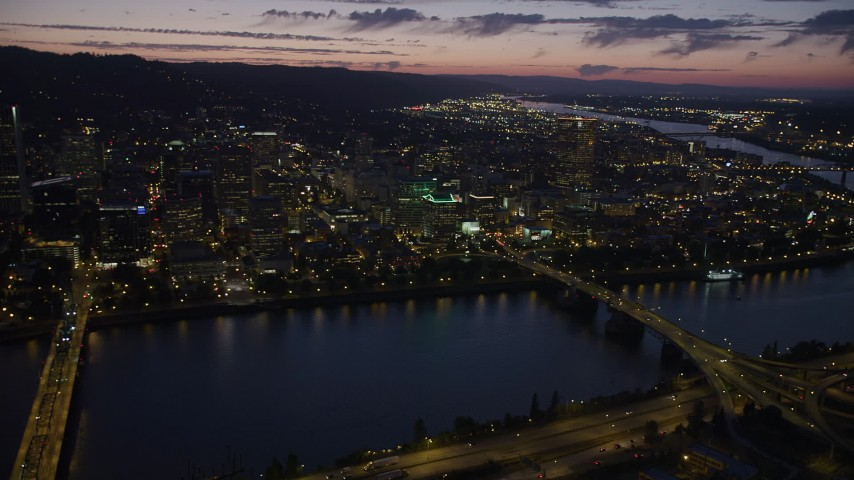 Flying by downtown, seen from Hawthorne Bridge, Downtown Portland, Oregon, night Aerial Stock Footage | AX55_012