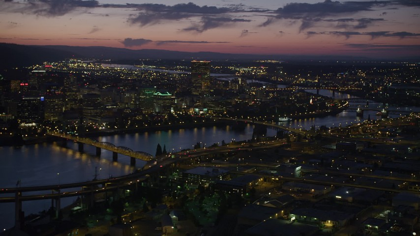 Flying by downtown and the Willamette River, seen from near Morrison Bridge, Downtown Portland, Oregon, night Aerial Stock Footage | AX55_015