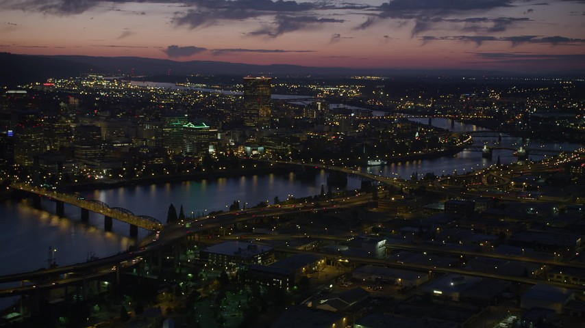 5K stock footage aerial video of flying by the city and the Willamette River, seen from near Morrison Bridge, Downtown Portland, Oregon, twilight Aerial Stock Footage | AX55_015