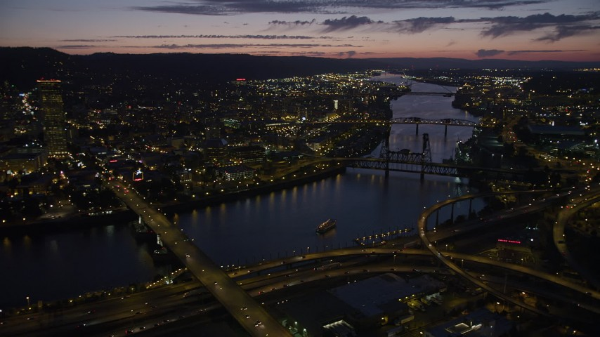 5K stock footage aerial video of US Bancorp Tower and bridges along the Willamette River, Downtown Portland, Oregon, twilight Aerial Stock Footage | AX55_018