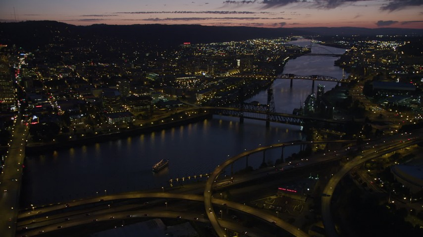 5K stock footage aerial video of flying by bridges along the Willamette River to Downtown Portland, Oregon, twilight Aerial Stock Footage | AX55_019