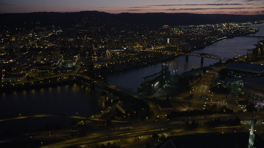 Flying by Steel Bridge and Broadway Bridge leading into Downtown Portland, Oregon, night Aerial Stock Footage | AX55_020