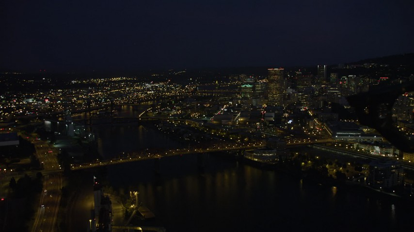 5K stock footage aerial video pan from Memorial Coliseum and the Broadway Bridge to reveal Downtown Portland, Oregon, night Aerial Stock Footage | AX55_024