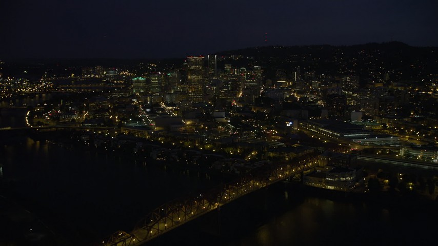 5K stock footage aerial video of crossing Willamette River and Broadway Bridge, approach US Bancorp Tower, Downtown Portland, night Aerial Stock Footage | AX55_026