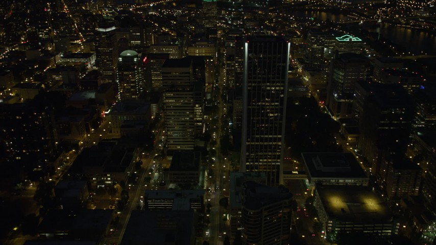 5K stock footage aerial video follow SW 5th Avenue by Wells Fargo Center, Downtown Portland, Oregon, night Aerial Stock Footage | AX55_032