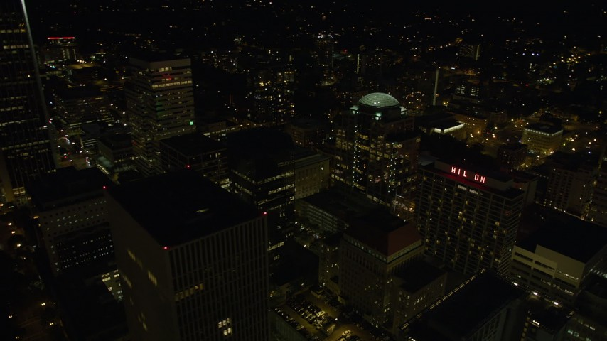 5K stock footage aerial video of flying by downtown buildings and 1000 Broadway in Downtown Portland, Oregon, night Aerial Stock Footage | AX55_047