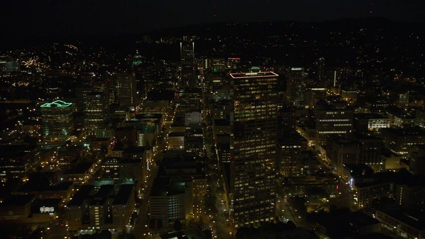 5K stock footage aerial video of flying by US Bancorp Tower, and toward Wells Fargo Center, Downtown Portland, Oregon, night Aerial Stock Footage | AX55_053
