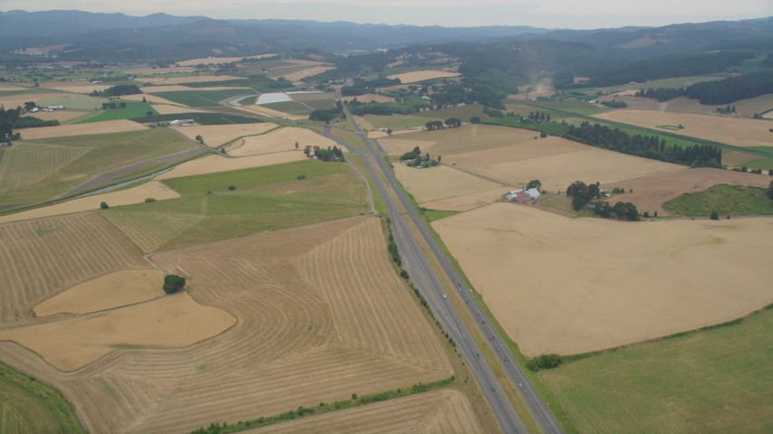 5K stock footage aerial video of following Highway 26 past farmland to Highway 6 split, Banks, Oregon Aerial Stock Footage | AX56_009