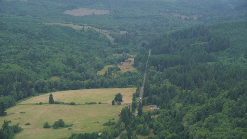 5K stock footage aerial video of country road between farms and evergreen trees in Clatsop County, Oregon Aerial Stock Footage | AX56_038