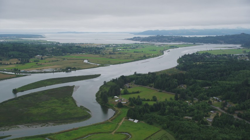 5K stock footage aerial video approach and pan across the Youngs River with farm fields by the water in Astoria, Oregon Aerial Stock Footage AX56_066 | Axiom Images