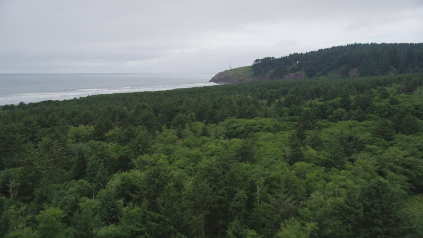 5K stock footage aerial video fly over Cape Disappointment State Park to approach North Head Light, Ilwaco, Washington Aerial Stock Footage | AX56_104