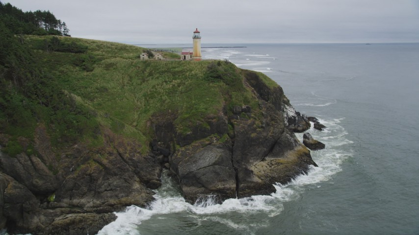 5K stock footage aerial video fly over green cliff, revealing North Head Light, Ilwaco, Washington Aerial Stock Footage | AX56_110
