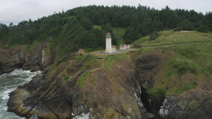 5K stock footage aerial video of an orbit of the North Head Light, on a cliff overlooking the ocean in Ilwaco, Washington Aerial Stock Footage | AX56_117