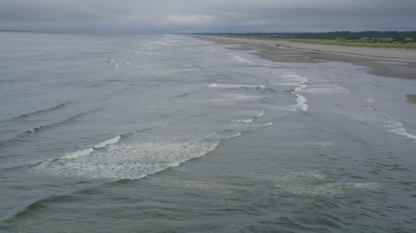5K stock footage aerial video fly over waves crashing into a beach around a  lone beachgoer in Seaview, Washington
